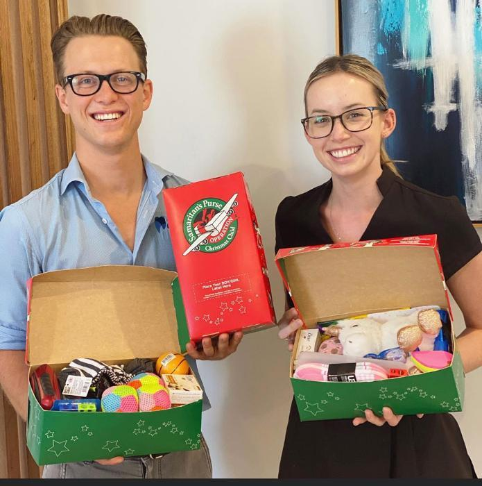 team members holding christmas gifts | Coffs Harbour Dentist