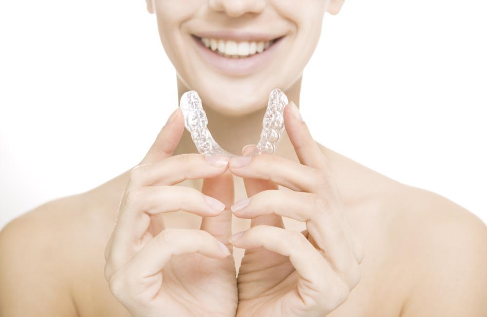 a woman holds her invisalign aligner | invisalign coffs harbour