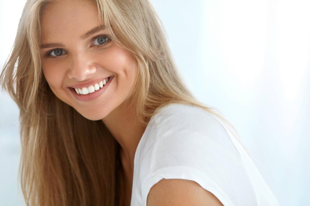a woman smiles in front of a white backdrop | dentist in coffs harbour nsw