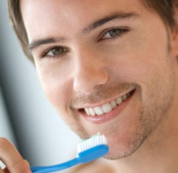 a man smiles and brushes his teeth | dentist coffs harbour