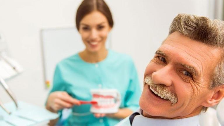 a man smiles in the dental office | dentist in coffs harbour