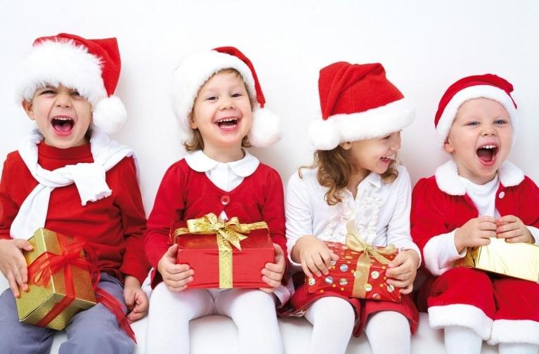 a group of children in santa costumes smiles