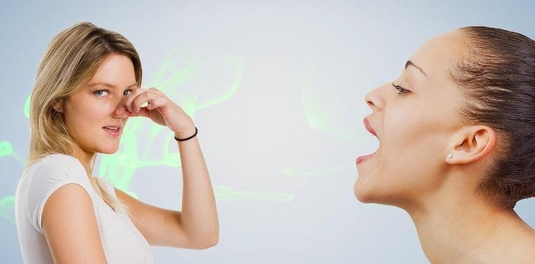 a woman plugs her nose as another breaths towards her | dentist in coffs harbour nsw