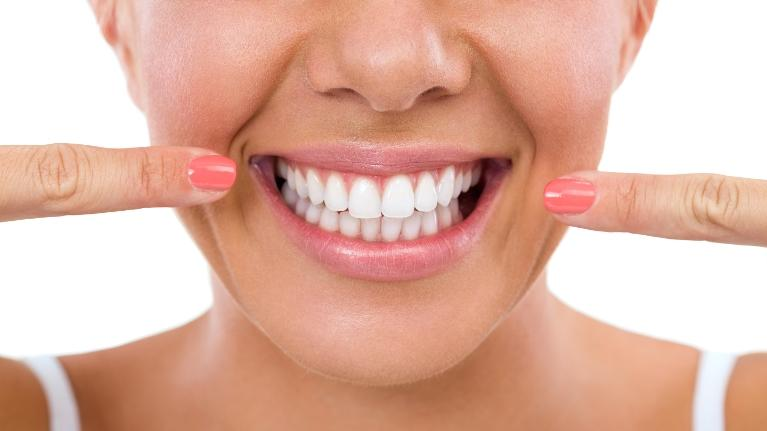 Woman pointing to her white teeth | Coffs Harbour Dentist